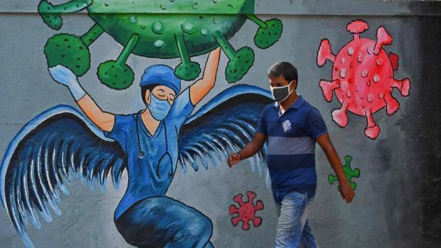 A pedestrian walks past a wall mural representing awareness measures against Covid-19 in Navi Mumbai on June 7, 2021.