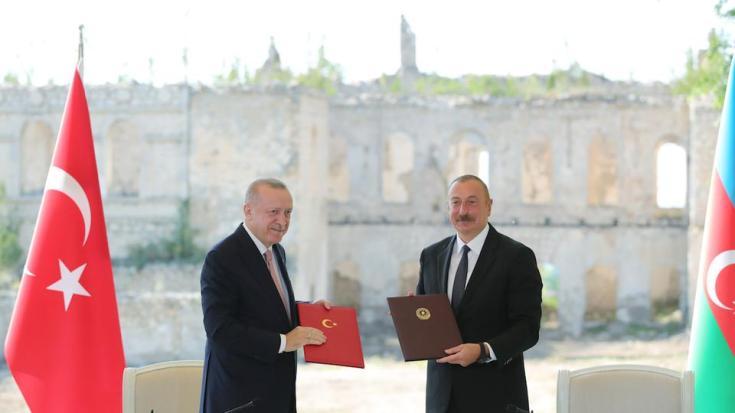 Turkish President Recep Tayyip Erdogan (L) and Azerbaijani President Ilham Aliyev (R) shake hands after signing