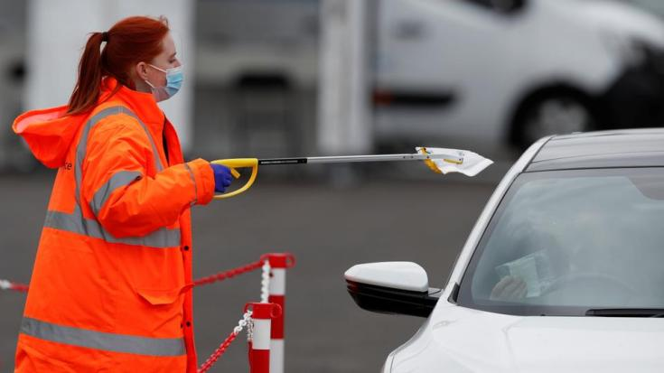 Staff member collects PCR tests for Covid-19 from members of the public, who have done a test in their own car, at a mobile testing unit at Oasis Beach Swimming Pool in Bedford, Britain May 25, 2021.