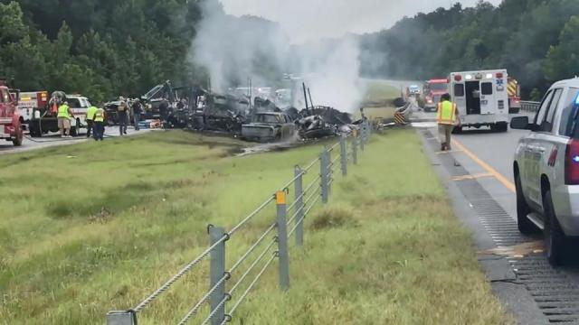 Emergency personnel work at the accident site as smoke rises from the wreckage after about 18 vehicles slammed together on a rain-drenched Alabama highway during Tropical Storm Claudette, in Butler County, Alabama, US, on June 19, 2021