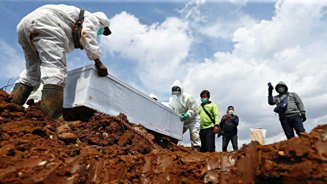 Municipality workers, wearing personal protective equipment, prepare to bury the coffin of a Covid-19 victim at a burial area, as the outbreak continues, in Jakarta, Indonesia, on June 21, 2021.
