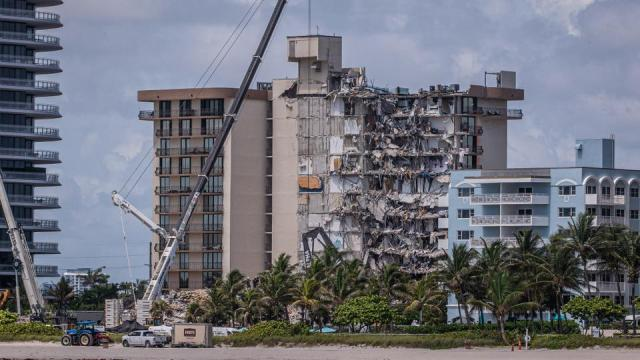 Members of the South Florida Urban Search and Rescue team look for possible survivors in the partially collapsed 12-story Champlain Towers South condo building on June 27, 2021 in Surfside, Florida.