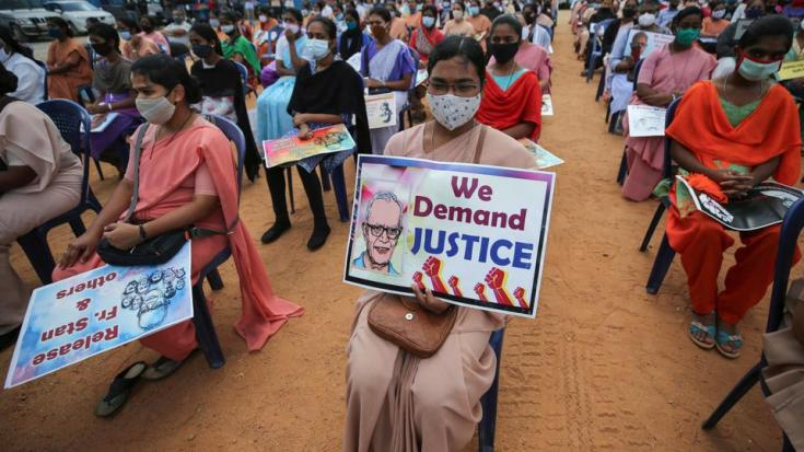A Christian nun, center, and others hold placards demanding the release of tribal rights activist Stan Swamy as they listen to a speaker during a demonstration in Bengaluru, India, Thursday, Nov.12, 2020.