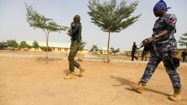 Police officers walk at the JSS Jangebe school, a day after over 300 school girls were abducted by bandits, in Zamfara, Nigeria February 27, 2021.