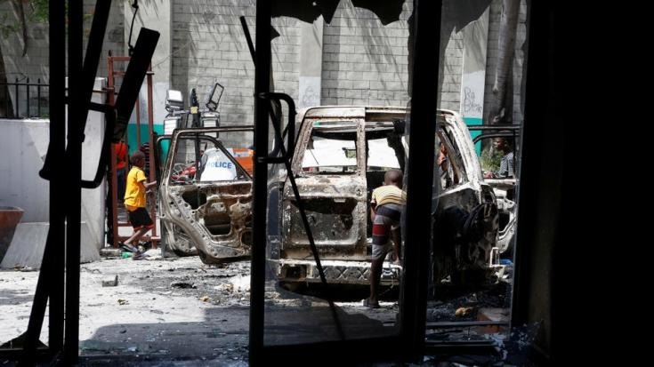 Children stand outside a house and next to a car, both burned after a firefight between police and suspected assassins of President Jovenel Moise, in Port-au-Prince, Haiti, July 8, 2021