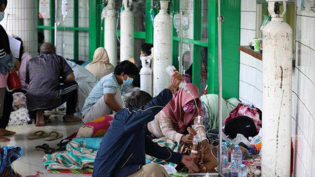 Oxygen tanks are prepared for patients in the hallway of an overcrowded hospital amid a surge of COVID-19 cases, in Surabaya, East Java, Indonesia, Friday, July 9, 2021