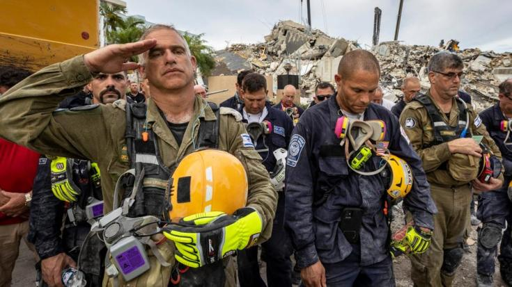 A member of the Israeli search and rescue team, left, salutes in front of the rubble that once was Champlain Towers South during a prayer ceremony, July 7, 2021, in Surfside, Fla.
