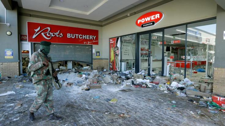 A patrolling soldier looks at damaged stores at a shopping centre in Soweto near Johannesburg on July 13, 2021.