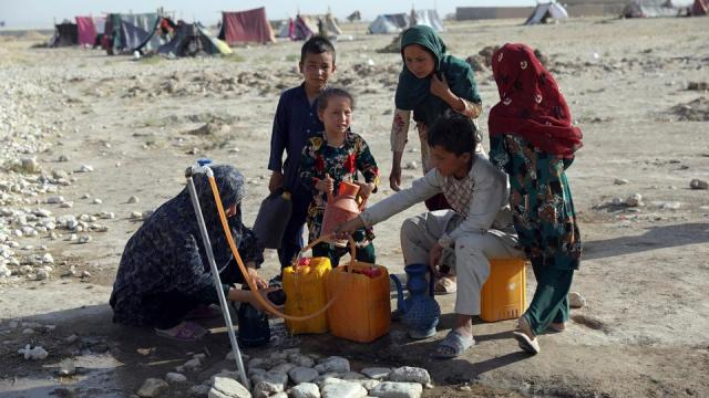 Internally displaced Afghans, who fled their home due to fighting between the Taliban and Afghan security personnel, fill water containers at a camp on the outskirts of Mazar-e-Sharif, northern Afghanistan, on Thursday, July 8, 2021