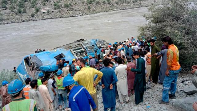Local residents and rescue workers gather at the site of bus accident, in Kohistan Kohistan district of Pakistan's Khyber Pakhtunkhwa province, Wednesday, July 14, 2021.
