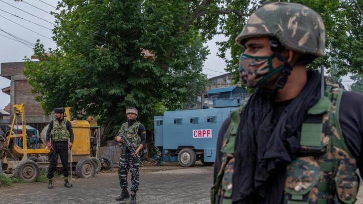 Indian paramilitary soldiers stand guard on a road leading towards the site of a gunfight in Pulwama, India-controlled Kashmir, on July 14, 2021.