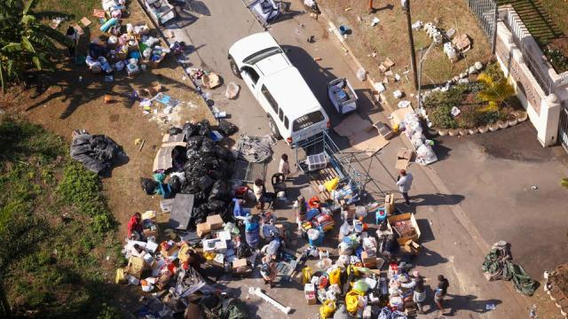 People loot an area near a burning warehouse after violence erupted following the jailing of former South African leader Jacob Zuma, in Durban, South Africa, July 14, 2021.