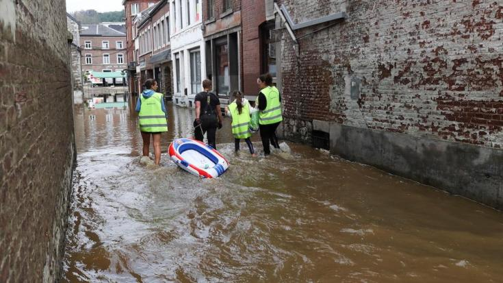 People walk through an area affected by floods, following heavy rainfalls, in Pepinster, Belgium, July 16, 2021.
