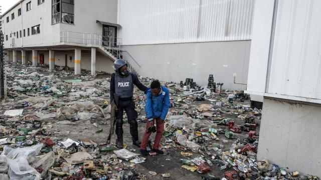 A member of SAPS detains a suspected looter outside a warehouse storing alcohol in Durban on July 16, 2021, in the midst of an ongoing alcohol ban after protestors have clashed with police following a week of unrest in South Africa.