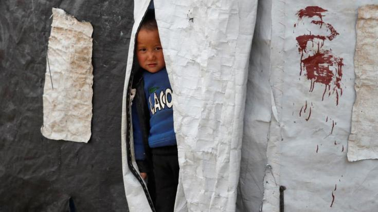 In this January 10, 2020 file photo, a boy looks out from inside a tent in al Roj camp, Syria.