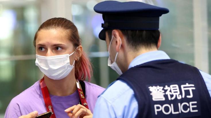Belarusian sprinter Krystsina Tsimanouskaya talks with police officers at Haneda international airport in Tokyo, Japan August 1, 2021.