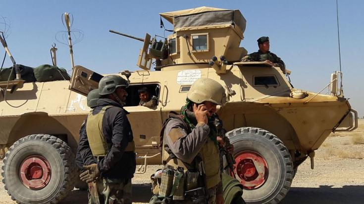 In this file photo from May 5, 2021, Afghan security forces stand near an armoured vehicle during ongoing fighting between Afghan security forces and Taliban insurgents in Busharan area on the outskirts of Lashkar Gah, the capital city of Helmand province.