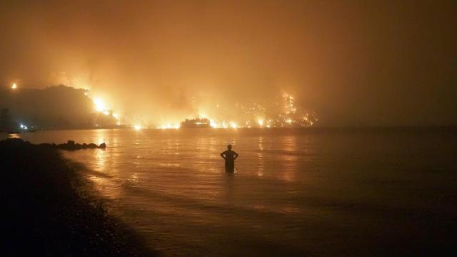 A man watches the flames as wildfire approaches Kochyli beach near Limni village on the island of Evia, about 160 kilometres (100 miles) north of Athens, Greece, late Friday, August  6, 2021.