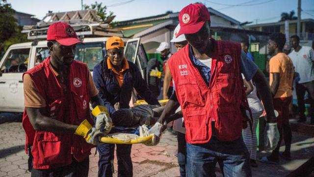Red Cross paramedics carry a girl injured during a 7.2 magnitude earthquake in Les Cayes, Haiti August 14, 2021.