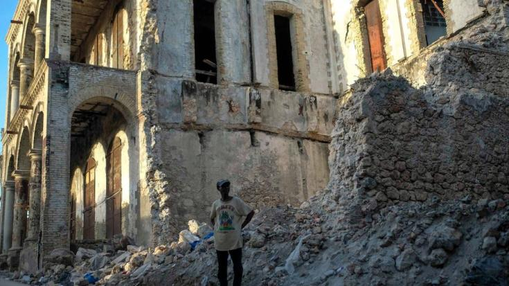 A man stands close to the rubble of a collapsed building in Jeremie, Haiti, Wednesday, Aug. 18, 2021.