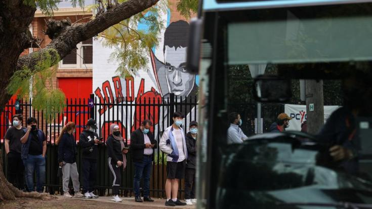 People wait in line outside a vaccination clinic in the Bankstown suburb during a lockdown to curb an outbreak of cases in Sydney, Australia, on August 25, 2021.