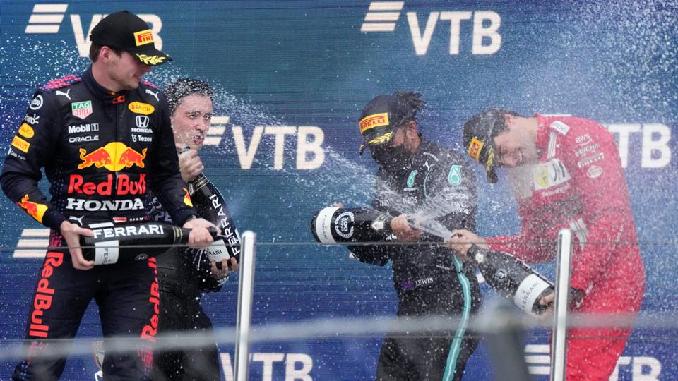 Mercedes' Lewis Hamilton, centre, celebrates on the podium after winning the race alongside second place Red Bull's Max Verstappen and third place Ferrari's Carlos Sainz Jr, Sochi, Russia, on September 26, 2021.