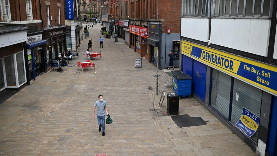 A pedestrian wearing a face covering due to Covid-19 walks past closed-down shops in Blackburn, north west England on June 16, 2021.