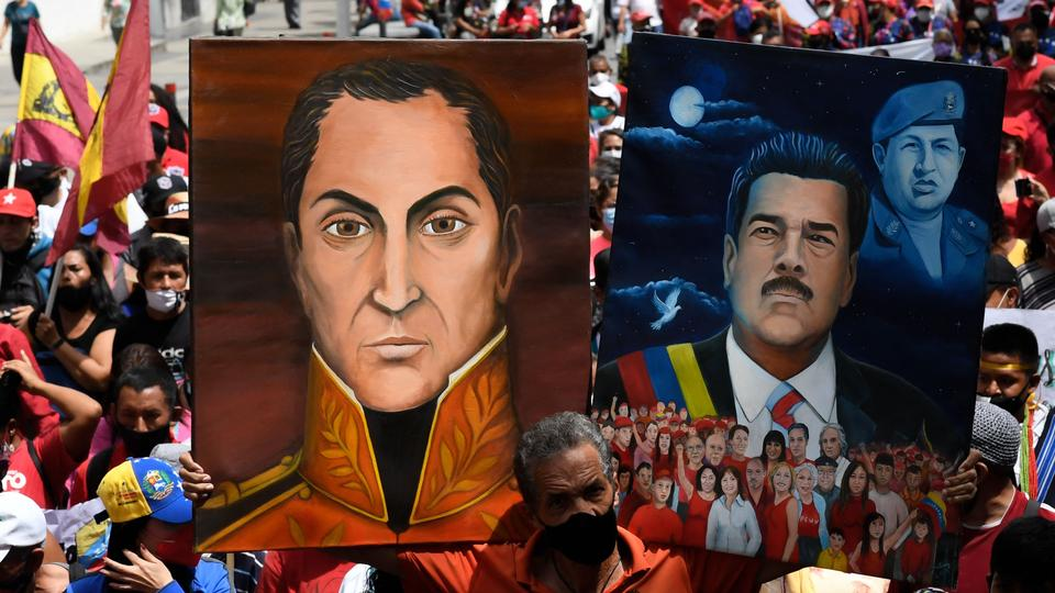 A supporter of Venezuela's President Nicolas Maduro, holds portraits of him (R) and Venezuela's national hero Simon Bolivar, during a march to commemorate the day of Indigenous Resistance, in Caracas, October 12, 2021.