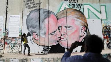 A man photographs a woman as she stands next to a mural depicting US President Donald Trump and Israeli Prime Minister Benjamin Netanyahu on the controversial Israeli barrier, in the West Bank city of Bethlehem October 29, 2017.