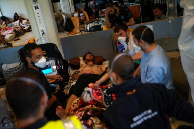 A Red Cross health worker calls an ambulance to transfer a man on hunger strike to a hospital as he occupies with others a big room of the ULB Francophone university in Brussels, Tuesday, June 29, 2021