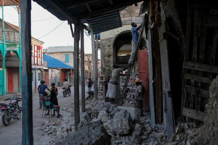 Men work on a damaged building in Jeremie, Haiti, Wednesday, Aug. 18, 2021.