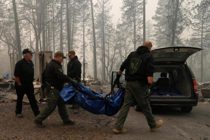 Yuba and Butte County Sheriff deputies carry a body bag with a deceased victim during the Camp fire in Paradise, California, US on November 10, 2018.