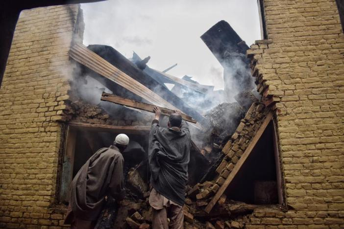 Local residents trying to take out smouldering wooden planks from the debris of what used to be the house of Bilal Ahmad, in South Kashmir's Kulgam district. Indian forces destroyed the house earlier this year.