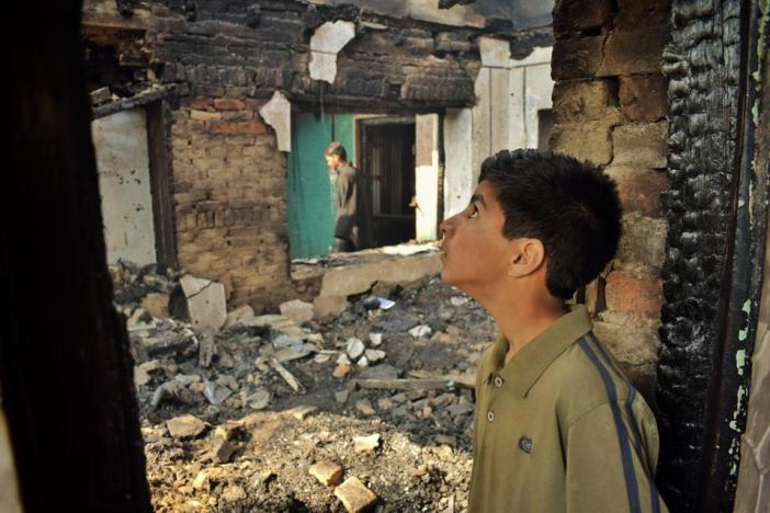 A boy looking at the debris of his house which was destroyed on April 1 this year by Indian forces in south Kashmir's Dailgam village.