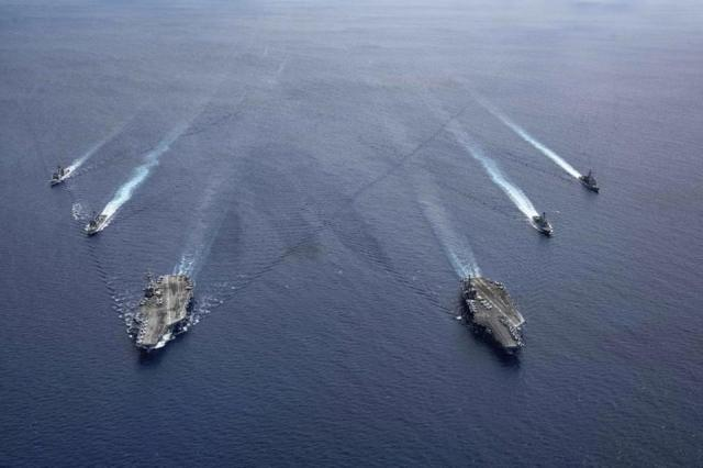 In this photo provided by U.S. Navy, the USS Ronald Reagan (CVN 76) and USS Nimitz (CVN 68) Carrier Strike Groups steam in formation, in the South China Sea, Monday, July 6, 2020.