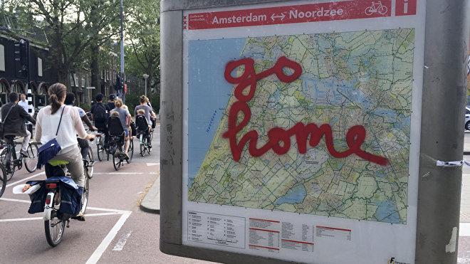 Grafiti sobre un mapa turístico en la ciudad de Ámsterdam:'Vallan a casa'
