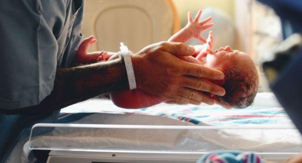 Un doctor sostiene a un bebé recién nacido