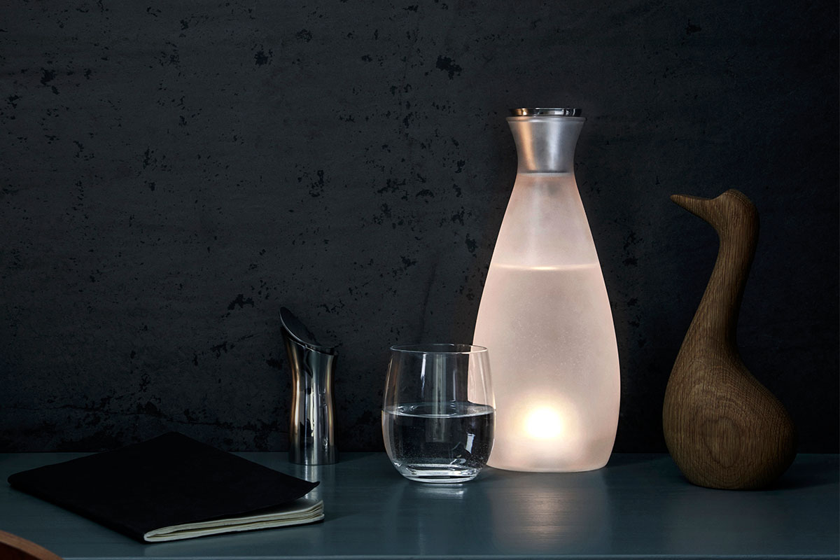 A carafe that lights up, next to a glass and book