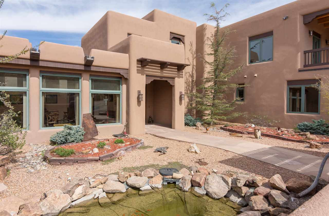 OPEN HOUSE! Sunday, 10/22 from 1 PM to 4 PM. Space and elegance take on a whole new meaning in this flawlessly executed and brilliantly designed SW pueblo-style home. Enjoy ever-changing, panoramic vistas of the Ortiz, San Pedro, Jemez and Sangre De Cristo Mountains. Soaring beamed ceilings, Italian porcelain tile, custom alder doors and cabinets, New Zealand granite, 3-story spiral staircase, media room, hobby room, office, workshop, wine cellar, energy efficient and sustainable and more. Elevate your expectations and enjoy prestigious and gracious living!
