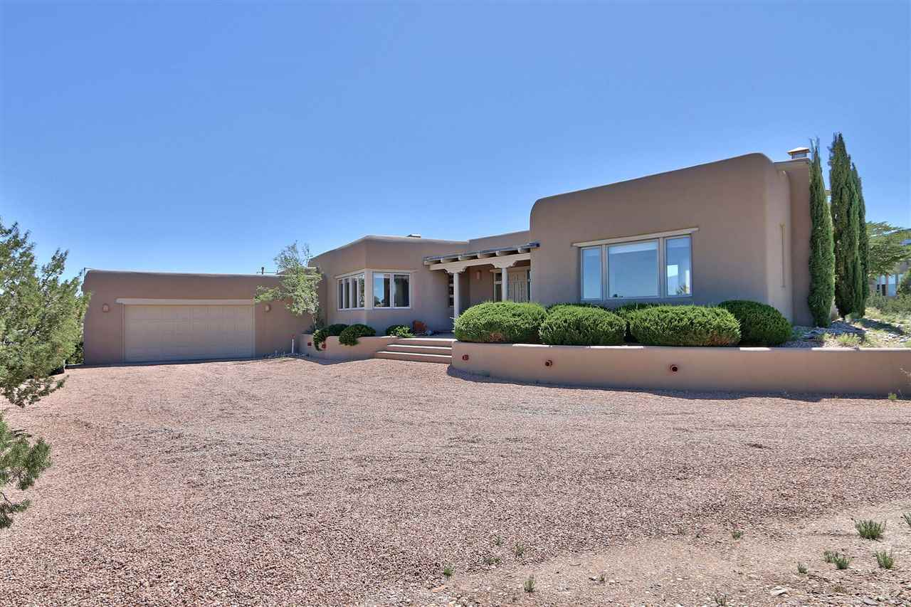 Classic SW adobe home by David Peterson.  Traditional design elements include brick floors, vigas, corbels and beautiful naturally light woodwork.  Gracious foyer leads to open entertaining areas.  Large picture windows frame the views of mountains and mesas.  True New Mexico living in the upscale La Mesa neighborhood.  Minutes from I-25 access in quiet and peaceful setting.  Local shopping close and 15 minutes to Paseo del Norte and city services.  Albuquerque a short 20 minute commute and 40 minutes to Santa Fe.  The best of both.  Community water and natural gas. Gorgeous house. Great value for adobe home.
