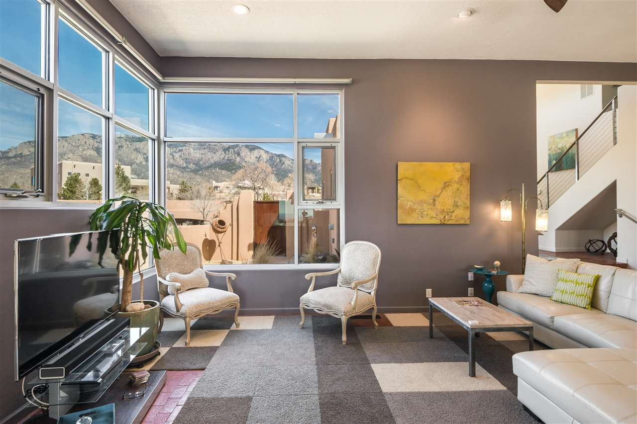 Contemporary perfection in High Desert! This sleek, modern home offers every high end amenity imaginable, beautifully decorated and wrapped in New Mexico vistas from every direction on large lot. Storefront windows, a pivoting front door and a large professionally landscaped walled yard are just a few upgrades that make this home a special place. A beautiful chef's kitchen equipped with Subzero refrigerator and ultra modern custom cabinets frame a view that spans over the city lights making this an entertainers dream. The upstairs master suite, with mountain views, has a master bath that houses custom built in closets & cabinetry and unparalleled views creating a glorious retreat after a long day. 2 other bedrooms each with ensuite baths. Don't miss this gracious and unique property!