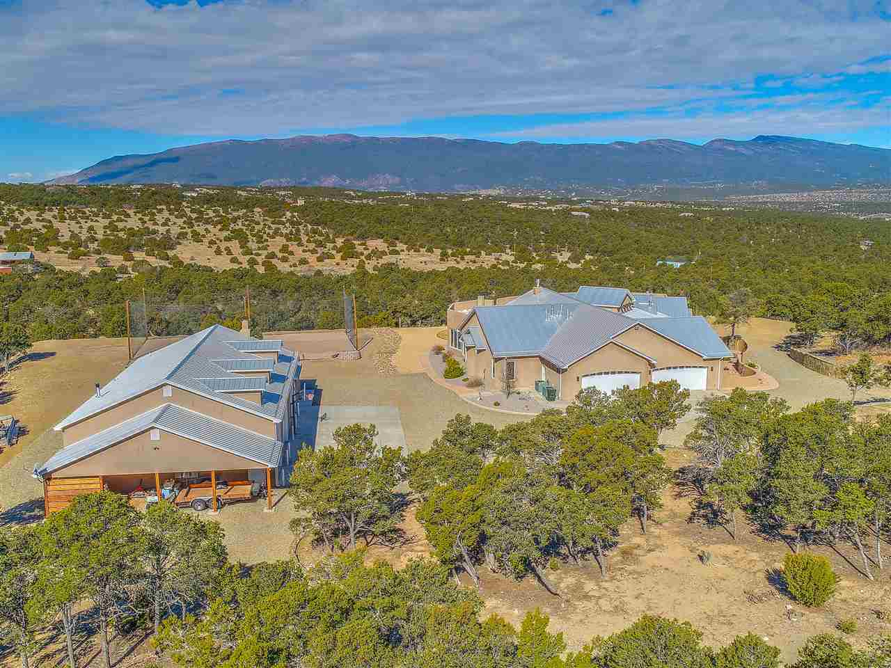 """Looking for Convenient, Quiet, and Green?  Would a truly spectacular view from every window interest you? 16 minutes to great shopping and theatres. 31 minutes to ABQ International Airport- really. This city-mountain retreat is the amazing gem you must see from a drone's perspective! Go now to the drone video link. A true Chef/Baker's Kitchen with Gourmet gas-top, oversized """"live-in"""" pantry room and top-of-the-Line cold food storage for superior meal-prep. Spectacular views while you cook and enjoy conversations in this modern great-room concept floorplan. Separate dining area provides for the more formal occasions or flex-use. Ambiance exudes throughout this high-end custom home with comfort features including on-demand fireplaces, radiant floor heating and refrigerated air conditioning. Ever heard of Barrett Jackson? This multiple garage estate is calling your name. Oversized auto toy-box with bathroom and conversation seating for your friends to enjoy.  Separate 4 car daily-driver coverage accesses the main home. RV garage stands adjacent to the flex-shop. Bringing some furry friends? Canine, Feline & Equines all welcome. Fully fenced with strategically placed pet entries and mountain pinon trees scattered throughout provide shade for Equine enjoyment. An impressive walled entry greets you with the convenience of electronic gated access. Bring the In-Laws! DETACHED, guest house is nicely finished and self-contained for extended visitors."""