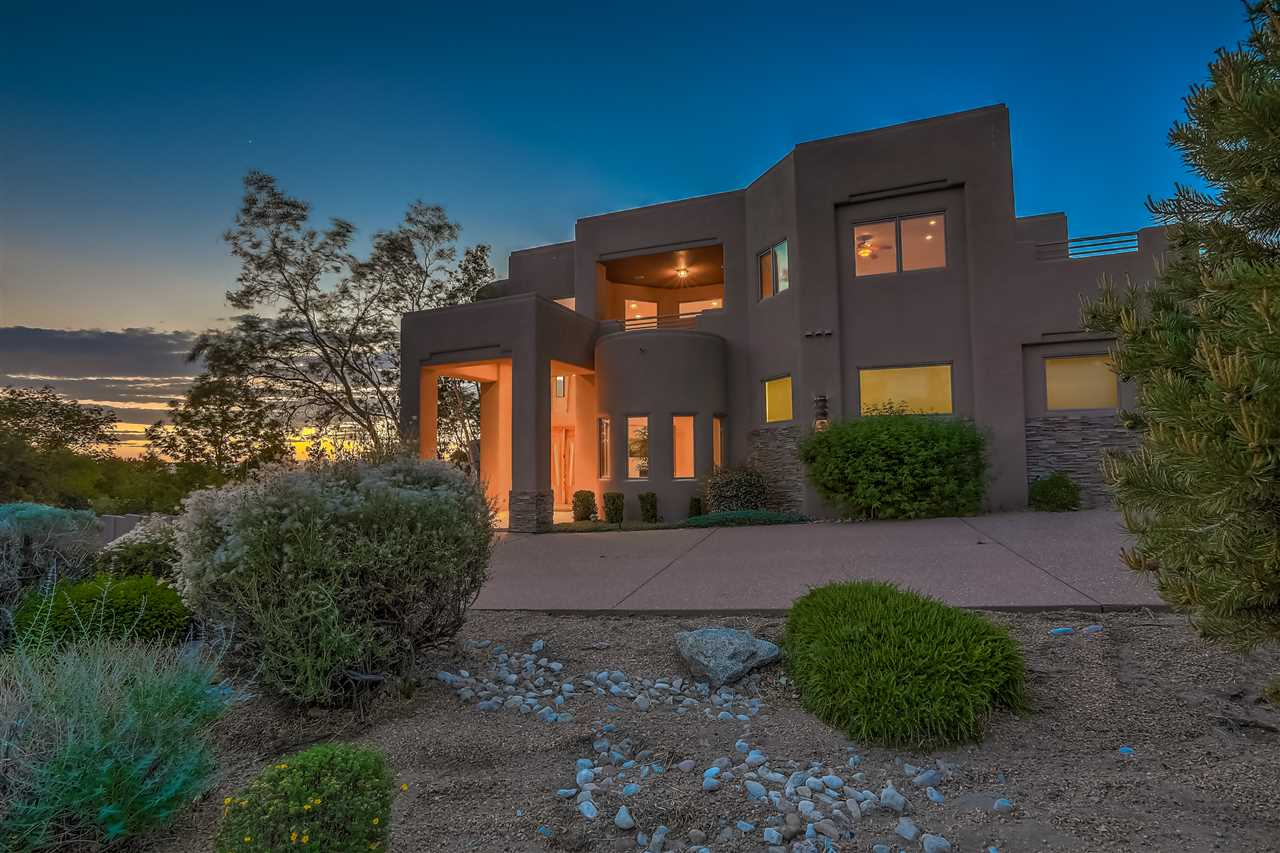 Enter through the custom carved-wooden door to a thoughtfully-designed home capturing the majestic Sandias and twinkling city lights from every window and deck. A home created for entertaining with open spaces and high ceilings for volume features large bar area with oversized wine frig. Truly a cook's kitchen with 5-burner gas stove, Sub-zero, prep sink and two dishwashers. Retire to the sound-proof media room with blackout shades. Abundance of space prevails in the large master with double closets, steam shower and jetted tub. A gracious upstairs living area with gas fireplace adjoins two additional bedrooms. There is an additional en-suite bedroom as well as a separate en-suite bedroom with separate entrance. Enjoy the outdoors and views from private patio, grill and bar with granite.