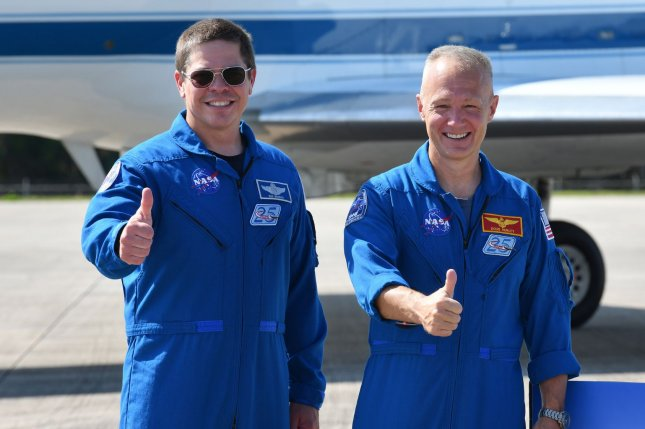 NASA Astronauts Bob Behnken (L) and Doug Hurley give the thumbs up after they arrive at Kennedy Space Center in Florida on Wednesday. Photo by Joe Marino/UPI