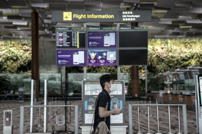 A man walks past a flight information board at Changi Airport in Singapore on October 5, 2020. Officials said Friday the VTL will operate between Changi and Incheon International Airport in South Korea. File Photo by Wallace Woon/EPA-EFE