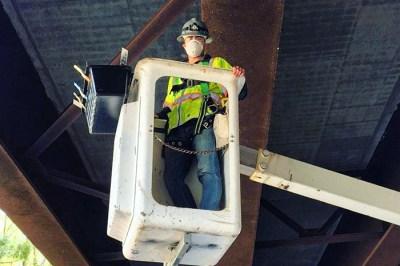 man in hardhat in bucket lift