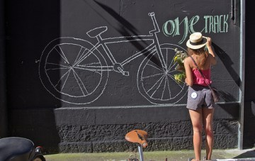 woman drawing a bicycle in chalk on a wall