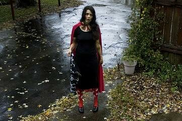 photo of femal zombie standing at bottom of front porch stairs