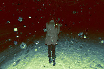 photo of woman walking in snow at nigh