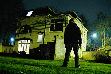 photo of man standing in front of a house at night